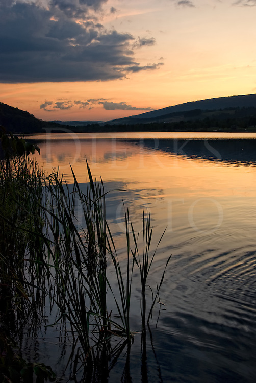 Sunset over lake water and reed with mountains behind, serenity in nature at Canoe Creek State Park, Hollidaysburg, Pennsylvania, PA, USA.