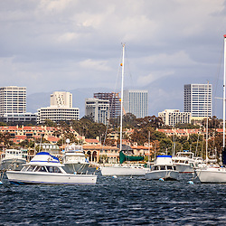Photo of Newport Beach skyline with boats in Newport Harbor, luxury homes and Newport Beach office buildings.  Newport Beach is a wealthy beach city along the Pacific Ocean in Orange County Southern California.