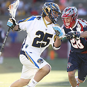 Davey Emala #25 of the Charlotte Hounds tries to get past Brent Adams #28 of the Boston Cannons during the game at Harvard Stadium on May 17, 2014 in Boston, Massachuttes. (Photo by Elan Kawesch)