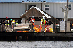 07 June 2010. Pointe aux Chenes, Louisiana.<br /> Fading away. Oil contractors prepare boom for loading into local boats as Jesus looks over them in the isolated town of Pointe Aux Chenes in Southe Louisiana. The town clings to the little land that remains along the bayous and waterways of southern Louisiana. Oil washes up on the  marsh grasses just south of tribal homes. If the grass dies, there is nothing left to hold the land. All of this was solid ground just 100 years ago. Diversion of the mighty Mississippi River diverted sediment from the wetlands and deposited precious land building material deep out at sea.  At present, all these fishing grounds are closed. Members of the Pointe aux Chenes Indians, settlers that can trace their roots beyond 5 generations back to France face extinction of their very way of life, their very existence. French cajun is the language of the elders, but is dying out in the children of today. BP's catastrophic oil spill threatens everything, their way of life and the land on which they live. Not recognised by the federal government, the 680 member tribe struggles for funds in a small community that survives only because of fishing and oil extraction in the Gulf of Mexico.<br /> Photo; Charlie Varley/varleypix.com