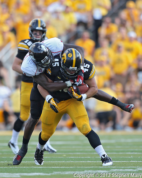 August 31 2013: Iowa Hawkeyes running back Mark Weisman (45) is brought down by Northern Illinois Huskies safety Dechane Durante (1) during the second half of the NCAA football game between the Northern Illinois Huskies and the Iowa Hawkeyes at Kinnick Stadium in Iowa City, Iowa on August 31, 2013. Northern Illinois defeated Iowa 30-27.