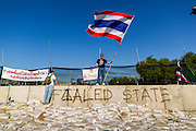 01 DECEMBER 2013 - BANGKOK, THAILAND:  An anti-government demonstrator waves a Thai flag on top of crowd control wall near Government House in Bangkok. Thousands of anti-government Thais confronted riot police at Phanitchayakan Intersection, where Rama I and Phitsanoluk Roads intersect, next to Government House (the office of the Prime Minister). Protestors threw rocks, cherry bombs, small explosives and Molotov cocktails at police who responded with waves of tear gas and chemical dispersal weapons. At least four people were killed at a university in suburban Bangkok when gangs of pro-government and anti-government demonstrators clashed. This is the most serious political violence in Thailand since 2010.   PHOTO BY JACK KURTZ