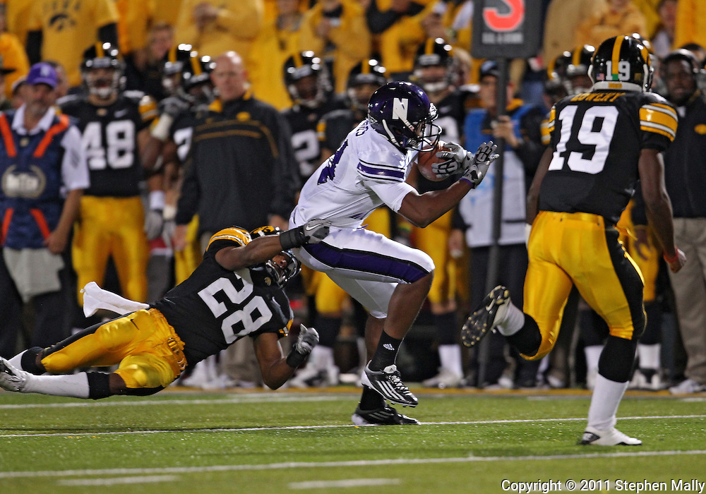October 15, 2011: Iowa Hawkeyes defensive back Shaun Prater (28) tries to pull down Northwestern Wildcats wide receiver Christian Jones (14) during the second half of the NCAA football game between the Northwestern Wildcats and the Iowa Hawkeyes at Kinnick Stadium in Iowa City, Iowa on Saturday, October 15, 2011. Iowa defeated Northwestern 41-31.