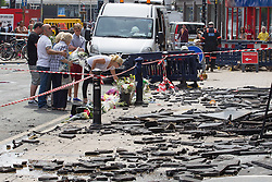 © Licensed to London News Pictures . FILE PICTURE DATED 15/07/2013 . Oldham Street , Manchester , UK . Stephen Hunt's family look at flowers and tributes at the scene . Son Sam (maroon shorts , 15), brother Christopher (white t-shirt, jeans, close cropped hair), grandmother Ruth (blue check shirt, dark trousers , red sunglasses), mother Susan (blue top, beige slacks, sunglasses), stepfather Wilf (dark hair, black t-shirt, grey shorts), daughter Charlotte (black and white sleeveless top, black pants, 18), sister Sarah (cream sleeveless top, blue jeans, dark hair, sunglasses) and ex-wife Zoe (white top, black pants, sunglasses) . The scene on Oldham Street following a fire at Paul 's Hair World on 13th July which claimed the life of fireman Stephen Hunt . Photo credit : Joel Goodman/LNP
