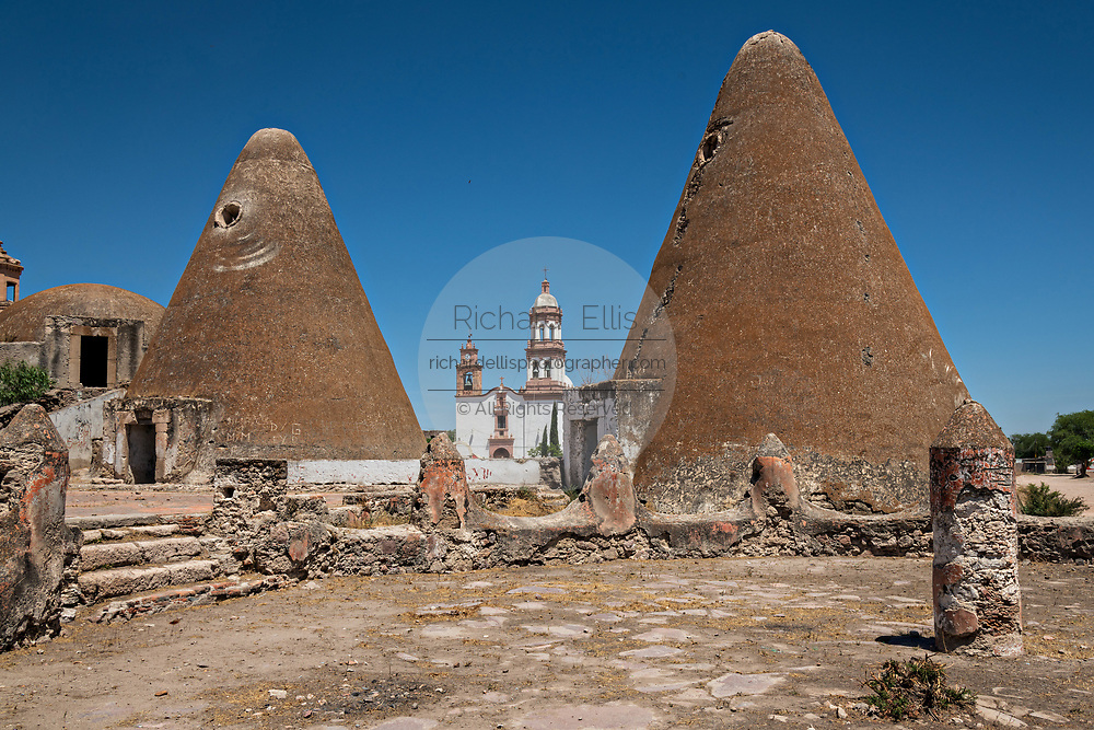 The Iglesia de San Diego De Alcalá church behind the pyramid shaped granaries at the Hacienda de Jaral de Berrio in Jaral de Berrios, Guanajuato, Mexico. The abandoned Jaral de Berrio hacienda was once the largest in Mexico and housed over 6,000 people on the property.