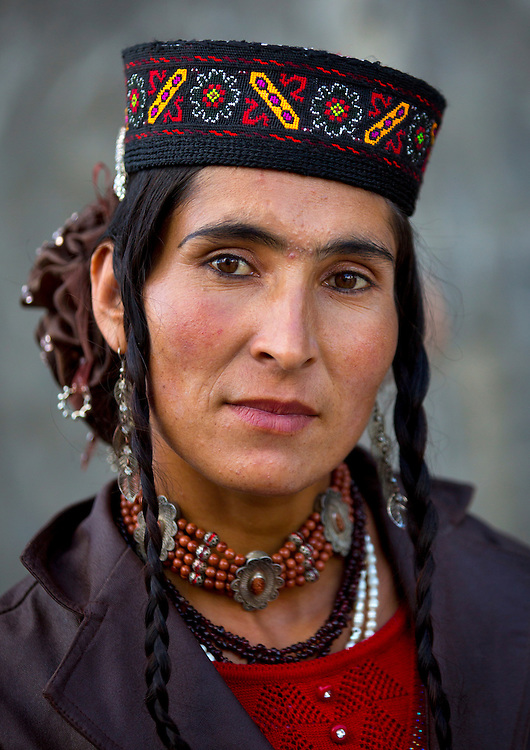 Tajik woman wearing colorful and embroidered jewelry, long braids, layered necklaces, earrings and ornaments carved in silver. Xinjiang Uyghur autonomous region, China.