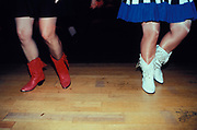 Two women in dresses and high leathere boots dancing, Lakeside, U.S.A, 1998.