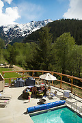 Hotel guests enjoy the sun pool side with Mt.Currie in the background.  Pemberton BC, Canada.