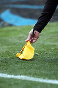 An official picks up his yellow penalty flag during the Carolina Panthers 2017 NFL week 15 regular season football game against the Green Bay Packers, Sunday, Dec. 17, 2017 in Charlotte, N.C. The Panthers won the game 31-24. (©Paul Anthony Spinelli)