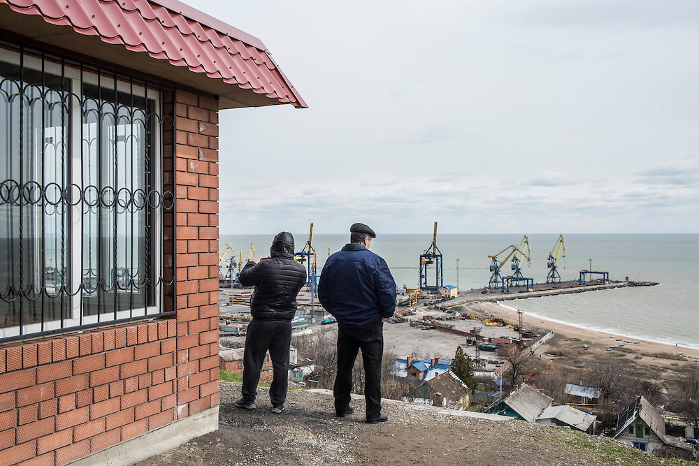 People look out over the city's port on Sunday, March 20, 2016 in Mariupol, Ukraine.