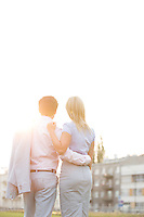 Rear view of business couple standing with arms around against clear sky on sunny day