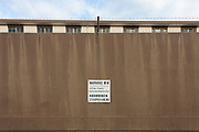A wall with a warning sign from the United States Navy, shields living quarters on the Naval Air Facility, Atsugi airbase near Yamato in Kanagawa, Japan, Wednesday February 13th 2019