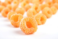 Close up of yellow raspberries on white background