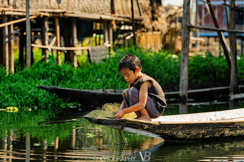 a young kid retrieving a fishing filet in a stilts vilage on the shore of inle lake, myanmar