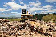 forestry machinery and timber lie abandoned amongst the typical rolling hills and green backdrop of the new zealand landscape at Mt Auckland, Rodney District, New Zealand