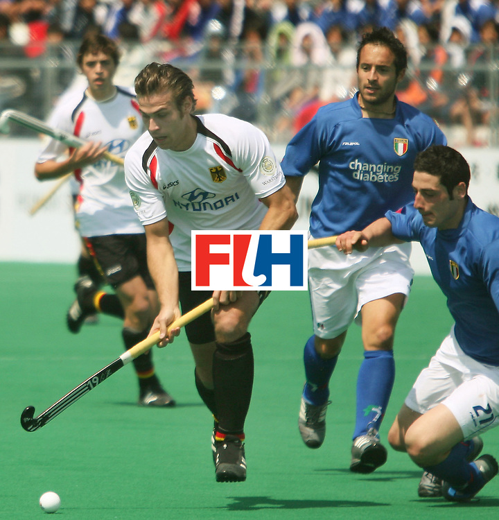 Kakamigahara, Gifu-Japan : Christopher Zeller of Germany gets the ball past Murgia Gabriele in the Olympic Hockey Qualifier at Gifu Perfectural Green Stadium at Kakamigahara on 05 April 2008. Christopher Zeller scored three goals. Germany beat Italy 8-0. <br /> Photo: GNN/ Vino John
