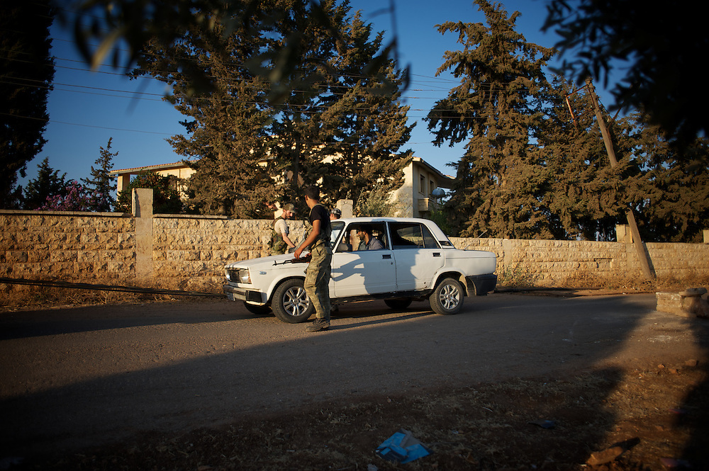 August 11, 2012 - Tarafat, Aleppo, Syria: Free Syria Army figthers stop a veihicle in a rebel checkpoint outside Tarafat village, near Aleppo. The Syrian Army warplanes have recently bombed residential areas and the only two schools in the village, with 200 kilogram bombs. (Paulo Nunes dos Santos/Polaris)