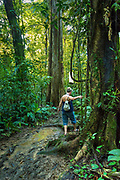 Tourist climbs around a pool of rainforest mud and water on one of the trails in the Tirimbina Biological Reserve.  The reserve is an educational, scientific, and ecotourism destination that protects 750 acres of rainforest in the Sarapiqui region of Costa Rica.