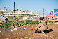 A Syrian boy living in the refugee camp at Atmeh, located in Idlib province near the Turkish border, kneels on the ground beside the border fence seperating his country and Turkey. A Turkish military post is on the hill on the other side of the fence.