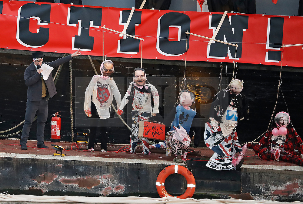 """© Licensed to London News Pictures. 26/11/2016. London, UK. JOE CORRE stands next to effigies of TONY BLAIR, GEORGE OSBORNE, DAVID CAMERON, BORIS JOHNSON and THERESA MAY wearing punk memorabilia. Joe Corre, the son of former Sex Pistol manager Malcolm McLaren and Vivienne Westwood burns his personal collection of Sex Pistols punk memorabilia. Earlier this week Joe Corre said that punk has become nothing more than a """"McDonald's brand ... owned by the state, establishment and corporations"""". His collection is estimated to be worth £5 million. Photo credit: Peter Macdiarmid/LNP"""