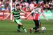 Forest Green Rovers Chris Clements(22) passes the ball past Cheltenham Town's Joe Morrell(25) during the EFL Sky Bet League 2 match between Cheltenham Town and Forest Green Rovers at LCI Rail Stadium, Cheltenham, England on 14 April 2018. Picture by Shane Healey.
