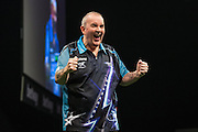 Phil Taylor hits the winning dart to beat Michael Smith during the Premier League Darts  at the Motorpoint Arena, Cardiff, Wales on 31 March 2016. Photo by Shane Healey.