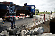 A police office leans against a closed umbrella as he watches over a truck crossing a bridge outside Lome, Togo on Thursday October 2, 2008.