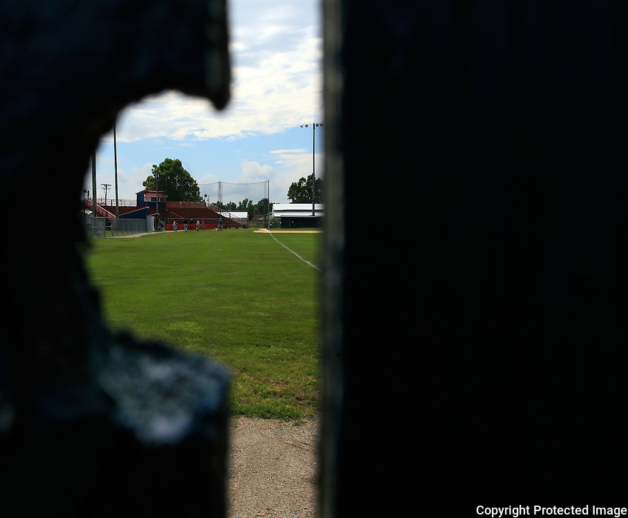 A knot hole in the wooden outfield fence provides a peak of Municipal Stadium from right field.  photo by David Peterson