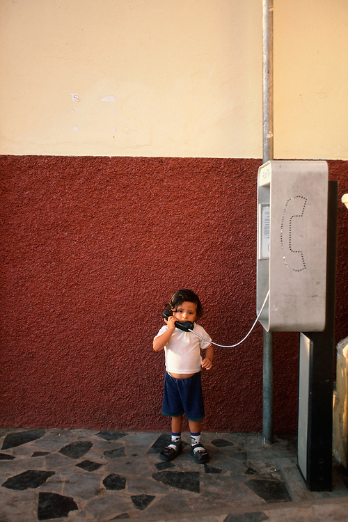 A small boy pretends to be talking on the phone in the Nicaraguan city of Leon.
