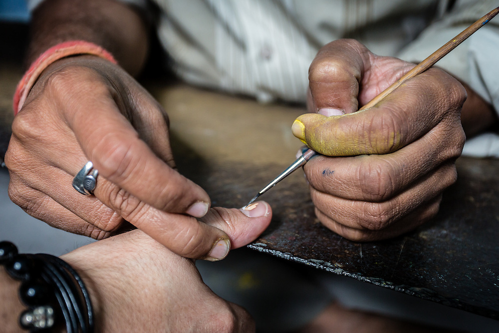 A traditional painter demonstrates his art by painting a small motif on a fingernail.