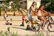 Israel, Kfar Yona, Children on rollerblades and bicycles play in a park