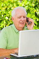Mature man talking on a cell phone and working with a laptop computer on outdoor patio table.