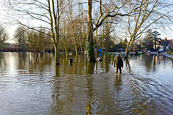 © Licensed to London News Pictures. 12/01/2014. Wraysbury, UK. A man uses a stick to walk through the floodwater. Flooding in Wraysbury, Berkshire today 12th January 2014.  Flooding and property damage is expected to continue along the River Thames.  Large areas of Britain are experiencing flooding after wet weather. Photo credit : Stephen Simpson/LNP