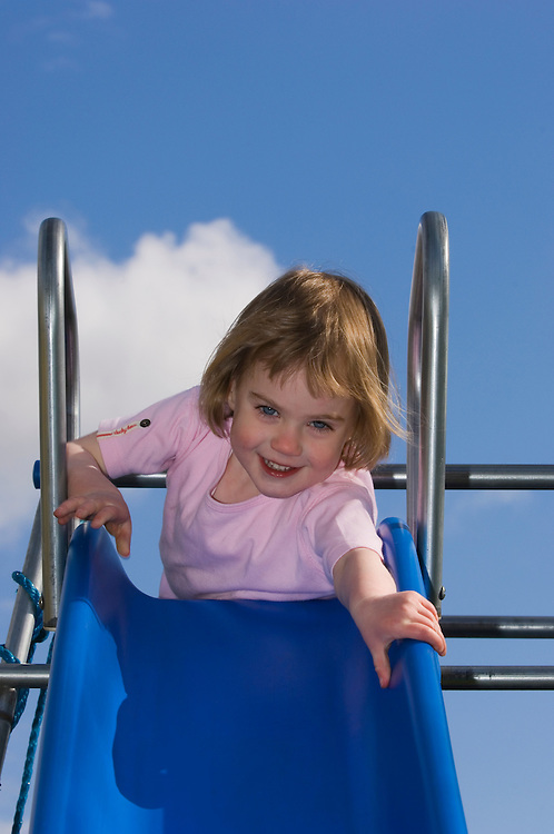 Girl, 3, about to go down a slide