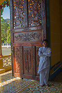 A vietnamese man stands at a doorway in Cao Dai Temple, Tay Ninh, Vietnam, Southeast Asia