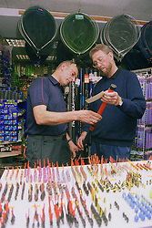 Two men working in fishing tackle shop examining fishing rod,