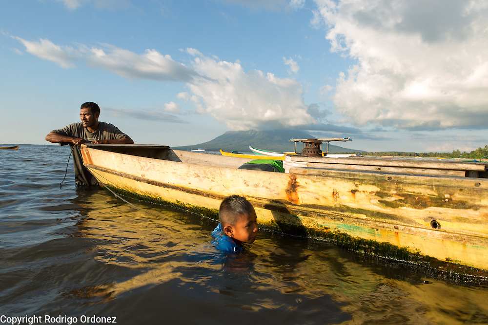 Fisherman Salmi Hasim, 31 (left), prepares his boat for a night of fishing while his son Irfan, 7, swims and plays in the water. They live in Kampung Nyamuk, a neighborhood of Lewoleba, Nubatukan subdistrict, Lembata district, East Nusa Tenggara province, Indonesia.