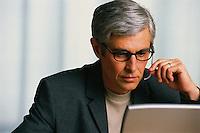 Telemarketer Working at Laptop --- Image by © Jim Cummins/CORBIS