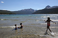 (R-L) Carla Villanueva, 9, Anahi Magana, 7, and Angelica Costa, 4, play in Redfish Lake on Saturday July 13, 2013, at the base of the Sawtooth Mountains in central Idaho outside of the town of Stanley.