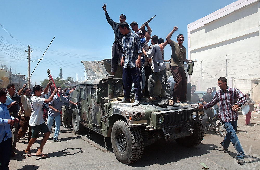 Iraqis dance upon a looted humvee near the scene of a house explosion in Northern Baghdad April 26, 2004.  A unit of U.S. soldiers were tricked into entering the booby trapped house after receiving a tip that chemical weapons were stored inside. .