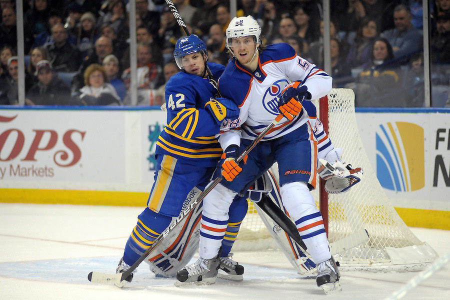 Buffalo Sabres left wing Nathan Gerbe (42) battles for position in front of the net with Edmonton Oilers defenseman Jeff Petry (58) during the second period at the First Niagara Center in Buffalo, New York. Edmonton and Buffalo are tied 2-2 after the second period.