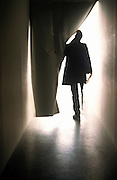 Man silhouetted against bright light as he walks through curtain