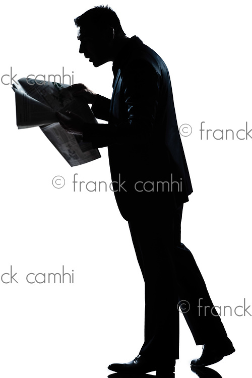 one caucasian man walking reading newspaper surprised  full length silhouette in studio isolated white background