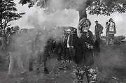 A man in a crowd of ravers waving a smoke flare, Upper chapel Rave, Brecon, Wales, August 2016.