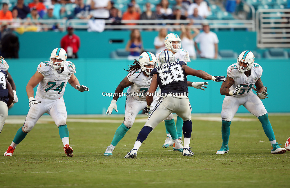 Miami Dolphins guard Billy Turner (77), Miami Dolphins tackle Jason Fox (74), and Miami Dolphins center Mike Pouncey (51) block while Dallas Cowboys defensive end Jack Crawford (58) rushes during the 2015 week 11 regular season NFL football game against the Dallas Cowboys on Sunday, Nov. 22, 2015 in Miami Gardens, Fla. The Cowboys won the game 24-14. (©Paul Anthony Spinelli)