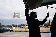 "MONTGOMERY, AL – JANUARY 25, 2016: Michael Harris, 52, prepares to load a customer's luggage at the Greyhound station on South Boulevard. In 2011, the downtown Montgomery Greyhound bus station was converted into a museum to honor the freedom riders, who endured a violent attack there in 1961. The replacement bus station, located four miles from downtown, is a prime business opportunity for independent cabbies like Michael Harris, who make a living serving passengers unwilling to rely on city buses. Many characterize the public bus system in Montgomery as unsafe and unreliable, so wary passengers cough up $2 per mile for trips in Mr. Harris' 2005 Lincoln Navigator, traveling across town for fast food, or sometimes as far as New York City. ""This is my life,"" Harris said. ""I love driving, and I help people out. It's just in my heart."""