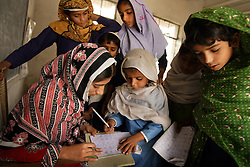 Nighat Parveen, a teacher, shows Uzma Ijaz, 4, how to write her ABC's at the girls school created by Mukhtar Mai, Meerwala, Pakistan, April 28, 2005. Mai, 33, went against the Pakistani tradition of committing suicide when she brought charges against the men who gang raped her nearly three years ago. With money from the ruling she opened two schools, one for girls, the other for boys, citing that education is the only thing that will stop such acts from happening.