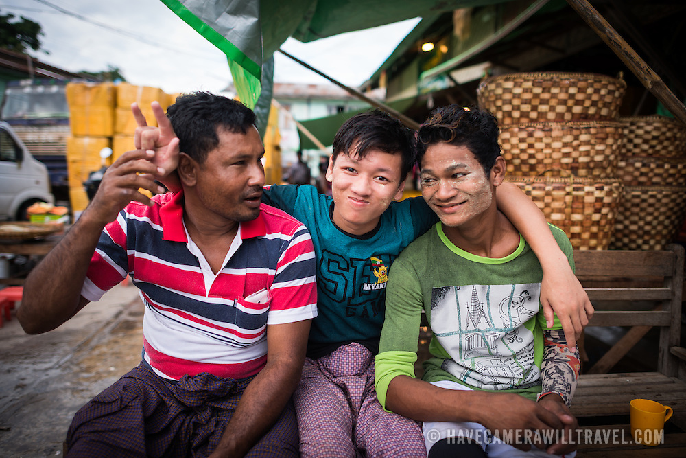 A group of three local men pose for a photo at the fish and flower market in Mandalay, Myanmar (Burma).