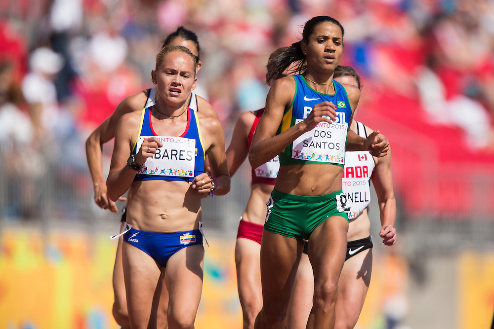 Julia Paula Dos Santos (R) of Brazil leads a pack of runners during the women's 5000 metres on the first day of athletics competition at the 2015 Pan American Games in Toronto, Canada, July 21,  2015. Dos Santos ran a personal best of 15:45.97 in the race to win the gold medal.  AFP PHOTO/GEOFF ROBINS