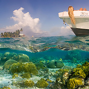 Girl resting in boat above coral reef with island in background, Belize Barrier Reef, Belize